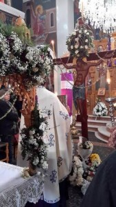 Good Friday service in Crete with flowers, priest and cross